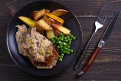 Стейк говядины diane с соусом гриба и лук-порея cream, фраями картошки и зелеными горохами стоковые фотографии rf