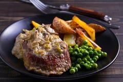 Стейк говядины diane с соусом гриба и лук-порея cream, фраями картошки и зелеными горохами стоковое изображение
