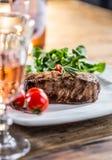 Стейк говядины стейк говядины сочный Изысканный стейк с овощами и стеклом розового вина на деревянном столе Стоковые Изображения