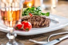 Стейк говядины стейк говядины сочный Изысканный стейк с овощами и стеклом розового вина на деревянном столе Стоковое Изображение RF
