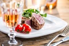 Стейк говядины стейк говядины сочный Изысканный стейк с овощами и стеклом розового вина на деревянном столе Стоковое Изображение