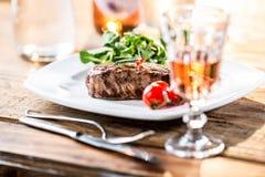 Стейк говядины стейк говядины сочный Изысканный стейк с овощами и стеклом розового вина на деревянном столе Стоковая Фотография