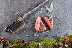 Стейк оленей или оленины с ингридиентами любит соль моря, травы и перец и сабля антиквариата, предпосылка еды для ресторана или h Стоковые Фотографии RF