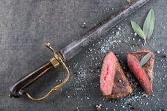 Стейк оленей или оленины с ингридиентами любит соль моря, травы и перец и сабля антиквариата, предпосылка еды для ресторана или h Стоковое Изображение