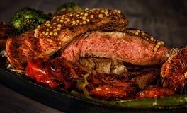 Стейк редкий с кровью, перец, чеснок, томаты, брокколи, зажарил в духовке на гриле, в сковороде дома стоковые фотографии rf