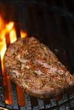 Стейк ростбифа глаза нервюры Ribeye на гриле барбекю bbq с пламенем Стоковые Изображения