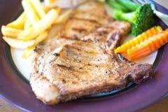Стейк свиной отбивной и зажаренные рыбы с салатом Стоковая Фотография