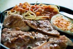 Стейк, спагетти, яичница на блюде лотка с вилкой и ложка цыпленка стоковая фотография