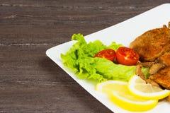 Стейк филе свинины с томатами вишни, лимоном и салатом в белом блюде на серой предпосылке Стоковые Фото