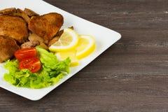 Стейк филе свинины с томатами вишни, лимоном и салатом в белом блюде на серой предпосылке Стоковая Фотография