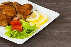 Стейк филе свинины с томатами вишни, лимоном и салатом в белом блюде на серой предпосылке Стоковые Изображения