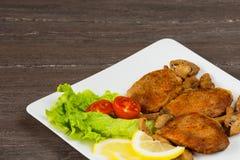 Стейк филе свинины с томатами вишни, лимоном и салатом в белом блюде на серой предпосылке Стоковая Фотография RF
