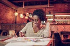 Стекла Афро-американской привлекательной женщины молод-взрослого нося писать детали в тетради стоковое фото rf
