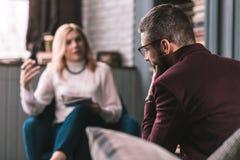 Стекла бородатого человека нося чувствуя обеспокоеный посещая терапевта стоковая фотография