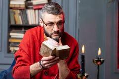 Стекла будущего упредителя нося читая меньшую старую книгу о divination стоковая фотография rf