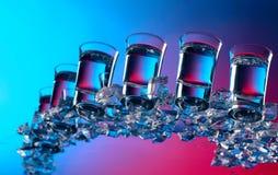 Стекла водки с льдом на стеклянном столе стоковое фото rf