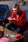 Стекла гадалки нося читая старую волшебную книгу о картах оракула стоковое изображение