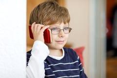 Стекла глаза милого мальчика маленького ребенка нося говоря на мобильном телефоне стоковое изображение rf