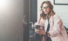 Стекла девушки битника нося и розовая куртка джинсовой ткани сидя в кофейне, выпивая кофе и говоря на сотовом телефоне Стоковое Изображение RF