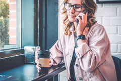 Стекла девушки битника нося и розовая куртка джинсовой ткани сидя в кофейне около окна Стоковые Фото