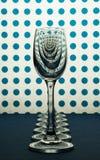 Стекла для настойки стоя в линии и белой предпосылке с голубыми пятнам стоковые изображения
