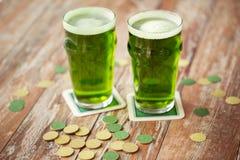 Стекла зеленых золотых монеток пива и на таблице Стоковая Фотография RF
