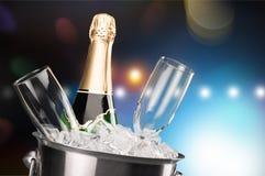 Стекла и бутылка шампанского в охладителе на свете Стоковая Фотография RF