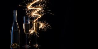 Стекла и бутылка шампанского в праздничных искрах Бенгалии Стоковые Фото