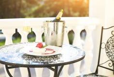 Стекла и десерт ith бутылки Шампани на таблице Стоковое Фото
