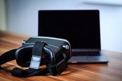 Стекла и компьтер-книжка VR на таблице символизируя цифровой учить стоковые изображения rf