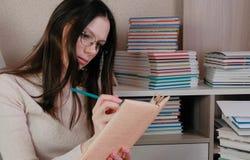 Стекла молодой женщины брюнет нося прочитали книгу делая примечания с карандашем Стоковая Фотография RF