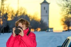Стекла молодой женщины нося, в зиме в красном photograp пальто стоковые фотографии rf