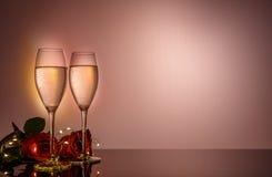 Стекла, настоящий момент и розы Шампани перед бежевой предпосылкой Стоковая Фотография
