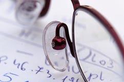 Стекла на предпосылке вычислений написанных рукой математически на куске бумаги стоковые изображения rf