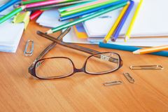 Стекла на предпосылке покрашенных карандашей и бумаги Стоковая Фотография