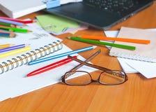 Стекла на предпосылке покрашенных карандашей и бумаги Стоковые Фото