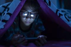 Стекла носки девушки используя мобильный телефон на темноте стоковая фотография