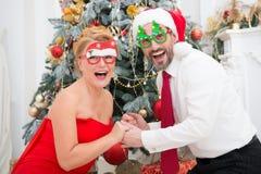 Стекла партии жизнерадостных стильных пар нося и сюрприз выражать с рождественской елкой на предпосылке стоковая фотография