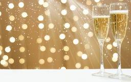 2 стекла пенясь шампанского на предпосылке праздничных гирлянд, космосе экземпляра для вашего текста на левой стороне Стоковое Фото