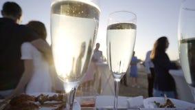 Стекла полные шампанского в свете захода солнца акции видеоматериалы