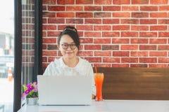Стекла прекрасной азиатской женщины нося сидя на кофейне с ноутбуком стоковое фото