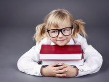 Стекла прелестной маленькой девочки нося и книги держать стоковые фотографии rf