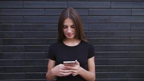 Стекла привлекательные молодой дамы нося используя телефон против предпосылки кирпичной стены Съемка конца-вверх стоковое фото
