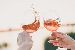 2 стекла розового вина в руках против неба захода солнца стоковое фото