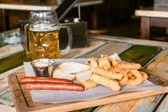Стекла светлого пива на предпосылке паба Стекло пинты золотого пива с закусками стоковые фотографии rf