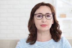 Стекла средние достигшие возраста женщины нося смотрят добросердечно на камере пока сидящ дома на кресле стоковое фото rf