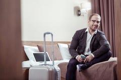 Стекла стильного человека нося сидя на кровати в гостиничном номере пока на командировке стоковые фото