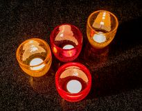Стекла с освещенными свечами на черной таблице Стоковая Фотография