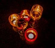 Стекла с освещенными свечами на черной таблице Стоковое Изображение RF