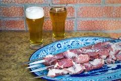 Стекла с пивом на таблице около подноса с shish kebab стоковая фотография